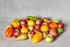 Mele, paprica, pera, arancia e limone sulla tela grigia Fotografie Stock Libere da Diritti