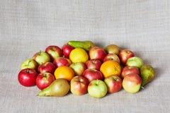 Mele, pera, limone ed arancia su una tela grigia Fotografie Stock Libere da Diritti
