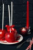Mele rosse casalinghe del rivestimento del caramello sull'bastoni per il Natale ed il nuovo anno Immagine Stock