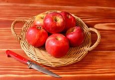 Mele rosse su un piatto di vimini con un coltello Fotografia Stock