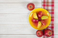 Mele su superficie di legno con la tovaglia a quadretti della cucina nella vista superiore Fotografia Stock Libera da Diritti