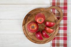 Mele su superficie di legno con la tovaglia a quadretti della cucina nella vista superiore Immagine Stock