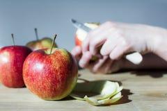 Mele su una tavola e sulle mani che sbucciano una mela Fotografia Stock Libera da Diritti