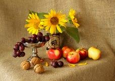 Mele, uva, girasoli e dadi sul fondo della tela da imballaggio Fotografia Stock Libera da Diritti