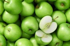 Mele verdi fresche luminose nelle goccioline di acqua, in mezzo alla mela tagliata, mele di verde del fondo dell'alimento Fotografia Stock