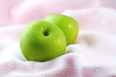 Mele verdi sul panno rosa Immagine Stock