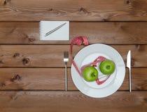 Mele verdi sul piatto con la forcella del coltello e nastro adesivo di misura Fotografia Stock Libera da Diritti