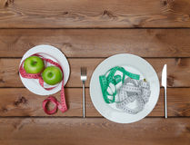 Mele verdi sul piatto con la forcella del coltello e nastro di misura su woode Fotografie Stock