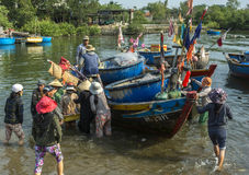 A melee erupts when a fishing sloop lands with fresh fish at a V Stock Photos