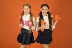 Melhorando seus energia e humor As meninas pequenas apreciam as estudantes bonitos do caf? da manh? da escola que guardam copos e foto de stock royalty free