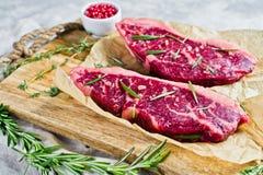 Melhore o bife do lombo em uma placa de desbastamento de madeira com alecrins e pimenta cor-de-rosa Fundo cinzento, vista superio imagens de stock
