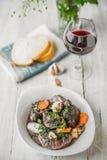 Melhore o bourguignon em uma placa cerâmica branca com um vidro do vinho Imagens de Stock