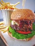 Melhore o hamburguer com as microplaquetas no fundo na bandeja de madeira fotos de stock