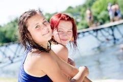 2 melhores amigas bonitas nas camisas molhadas da roupa que têm o assento de relaxamento do divertimento no banco do rio no Sandy Foto de Stock Royalty Free