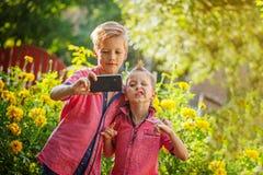 Melhores amigos Dois rapazes pequenos bonitos que fazem o selfie e que fazem o funn Fotografia de Stock Royalty Free
