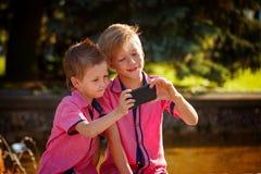 Melhores amigos Dois rapazes pequenos bonitos que fazem o selfie e que fazem o funn Fotos de Stock
