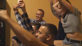 Melhores amigos felizes que olham o jogo dos esportes no portátil em casa Os suportes novos do futebol gritam com os bra?os aumen video estoque