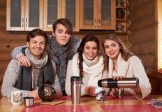 Melhores amigos que bebem o chá quente na cozinha confortável na casa de campo do inverno Imagem de Stock Royalty Free