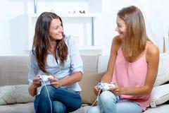 Melhores amigos que jogam jogos de v?deo imagem de stock royalty free