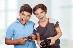 Melhores amigos que jogam no playstation Imagem de Stock