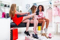 Melhores amigos que tentam nas sapatas diferentes que falam o assento em um banco em uma loja de roupa na moda da forma Fotografia de Stock Royalty Free