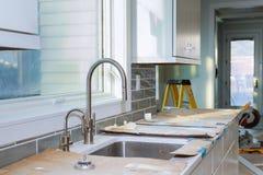 A melhoria da instalação dos armários de cozinha remodela o worm& x27; opinião de s instalada em uma cozinha nova imagens de stock