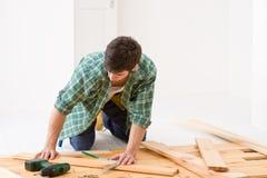Melhoria Home - homem que instala o assoalho de madeira Fotografia de Stock