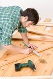 Melhoria Home - homem que instala o assoalho de madeira Imagem de Stock Royalty Free