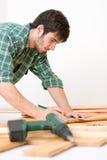 Melhoria Home - homem que instala o assoalho de madeira Foto de Stock Royalty Free