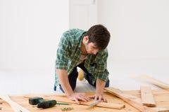 Melhoria Home - homem que instala o assoalho de madeira Fotografia de Stock Royalty Free