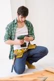 Melhoria Home - homem que instala o assoalho de madeira Fotos de Stock Royalty Free