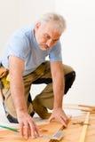 Melhoria Home - homem que instala o assoalho de madeira Imagens de Stock