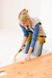 Melhoria Home - mulher que instala o assoalho de madeira Fotografia de Stock Royalty Free