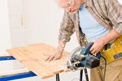 Melhoria Home - o trabalhador manual cortou a madeira com serra de vaivém Fotografia de Stock