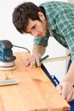 Melhoria Home - o trabalhador manual prepara o assoalho de madeira Fotos de Stock Royalty Free