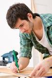Melhoria Home - o trabalhador manual prepara o assoalho de madeira Imagens de Stock