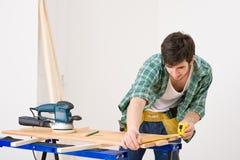 Melhoria Home - o trabalhador manual prepara o assoalho de madeira Imagens de Stock Royalty Free