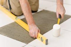 Melhoria Home - trabalhador manual que coloca a telha imagens de stock