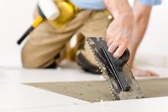 Melhoria Home - trabalhador manual que coloca a telha Fotografia de Stock Royalty Free