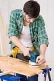 Melhoria Home - trabalhador manual que lixa o assoalho de madeira imagens de stock