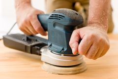 Melhoria Home - trabalhador manual que lixa o assoalho de madeira imagens de stock royalty free
