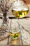 Melissa tea drops from teapot in glass cup on table Stock Photography