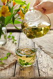 Melissa tea healthy beverage drops from teapot in cup Royalty Free Stock Images