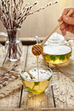 Melissa tea with honey in glass cup, teapot and willow Stock Images