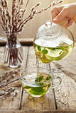 Melissa tea pouring in glass cup from transparent teapot Royalty Free Stock Images
