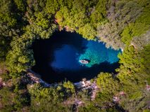 Melissani Cave Kefalonia viewed from above with tourists enterin. G the cave by boat aerial view Royalty Free Stock Photos