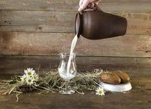 Melk die in een glas wordt gegoten Stock Foto
