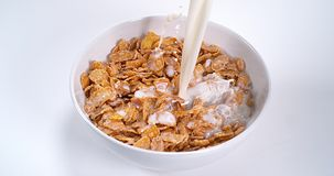 Melk die in een kom graangewassen stroomt, stock video