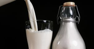 Melk die in Glas tegen zwarte Achtergrond worden gegoten, stock videobeelden