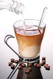 Melk die in kop van koffie wordt gegoten Stock Foto